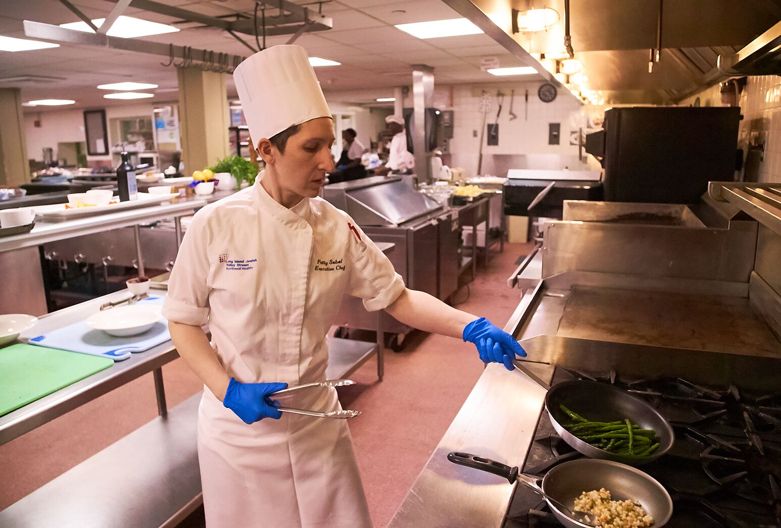 Chef prepares food on stove in hospital kitchen.
