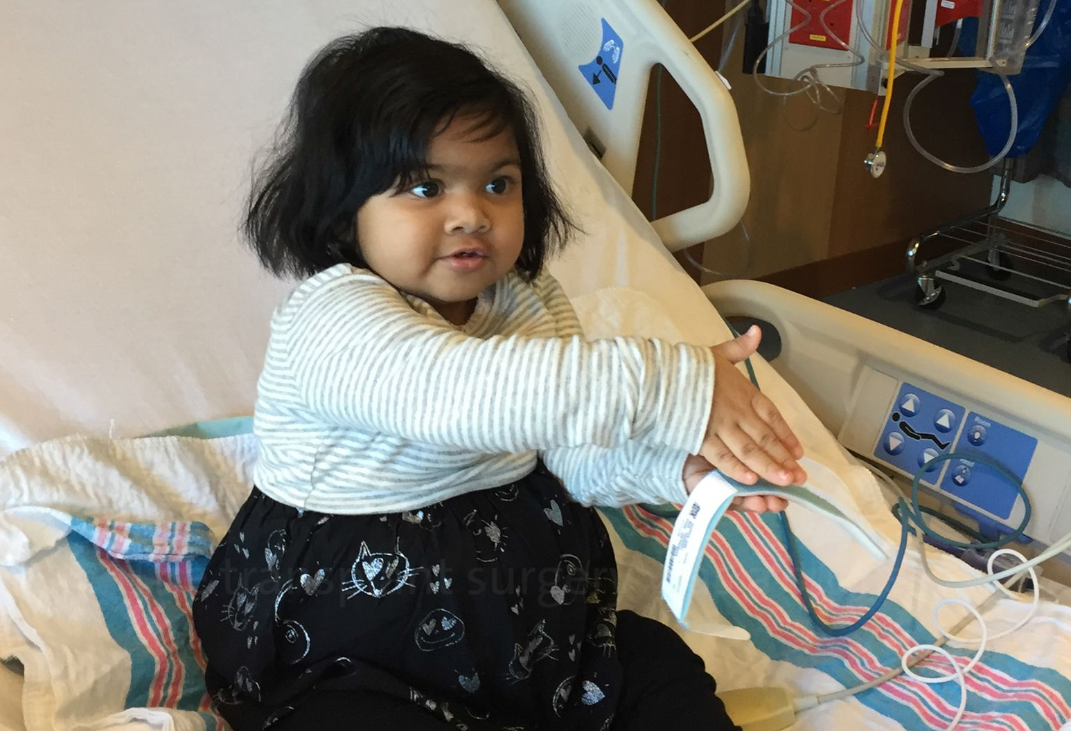 A girl toddler sits in a hospital bed wearing a dress with a black and gray cat print. She is playing with a hospital bracelet.