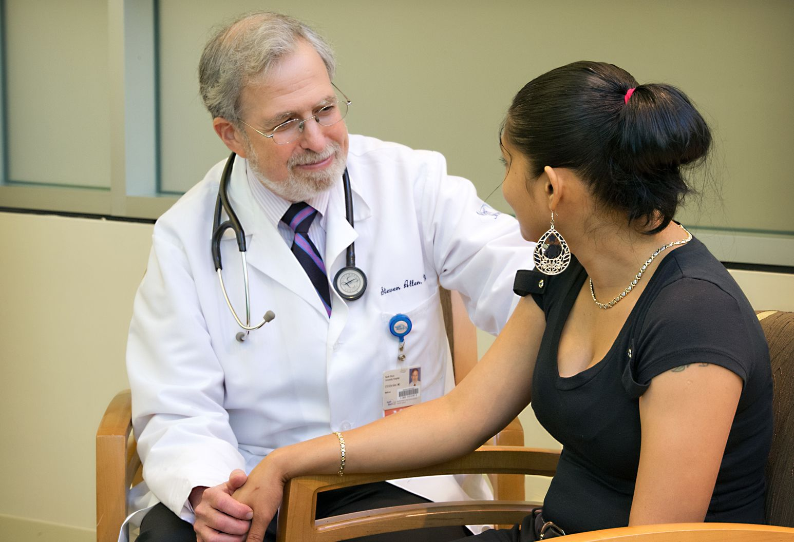 Physician sitting with patient, holding her hand reassuringly