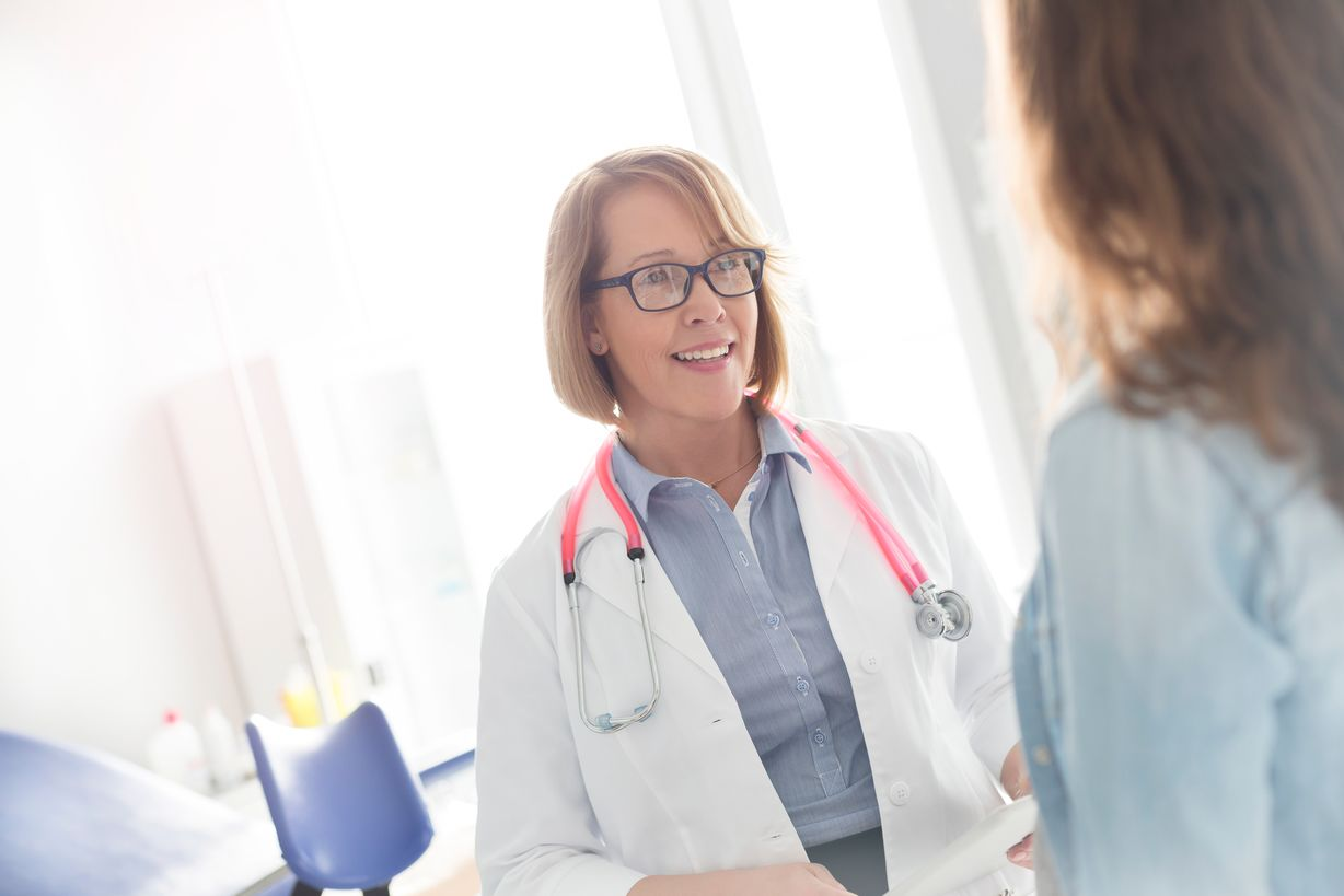 A female doctor with glasses, a white lab coat and a pink stethoscope looks toward a patient and smiles.