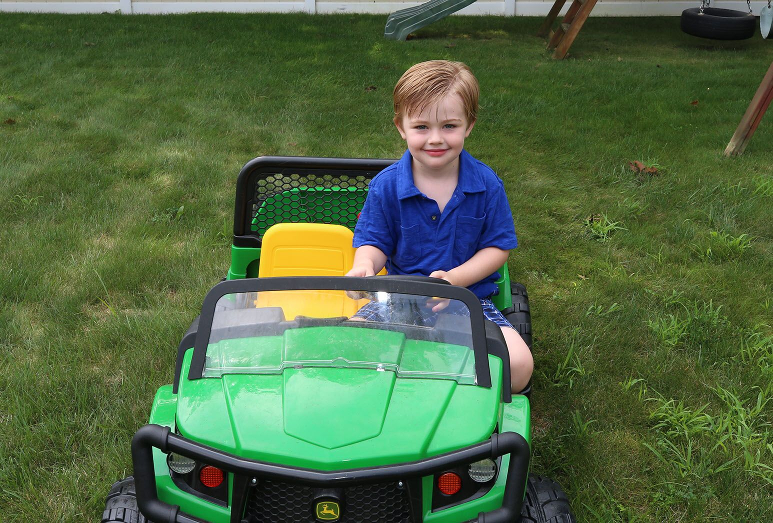 Young boy with blond hair in a blue shirt playing in a child-sized green truck.