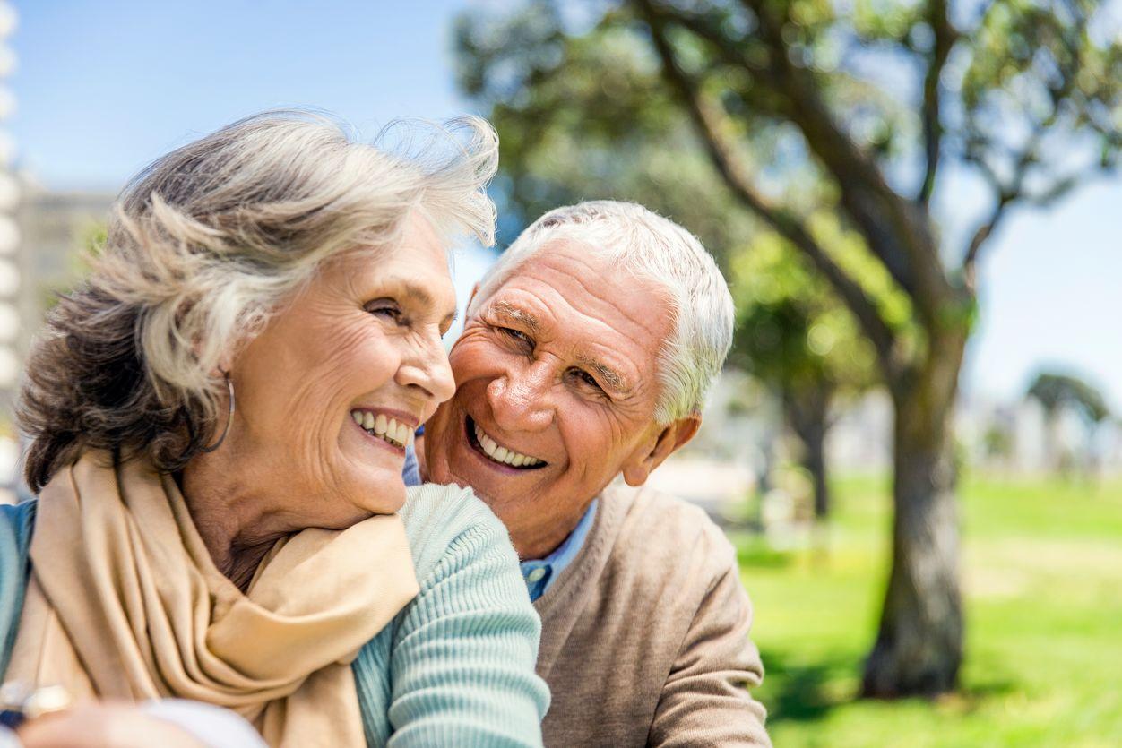 An elderly couple hugs