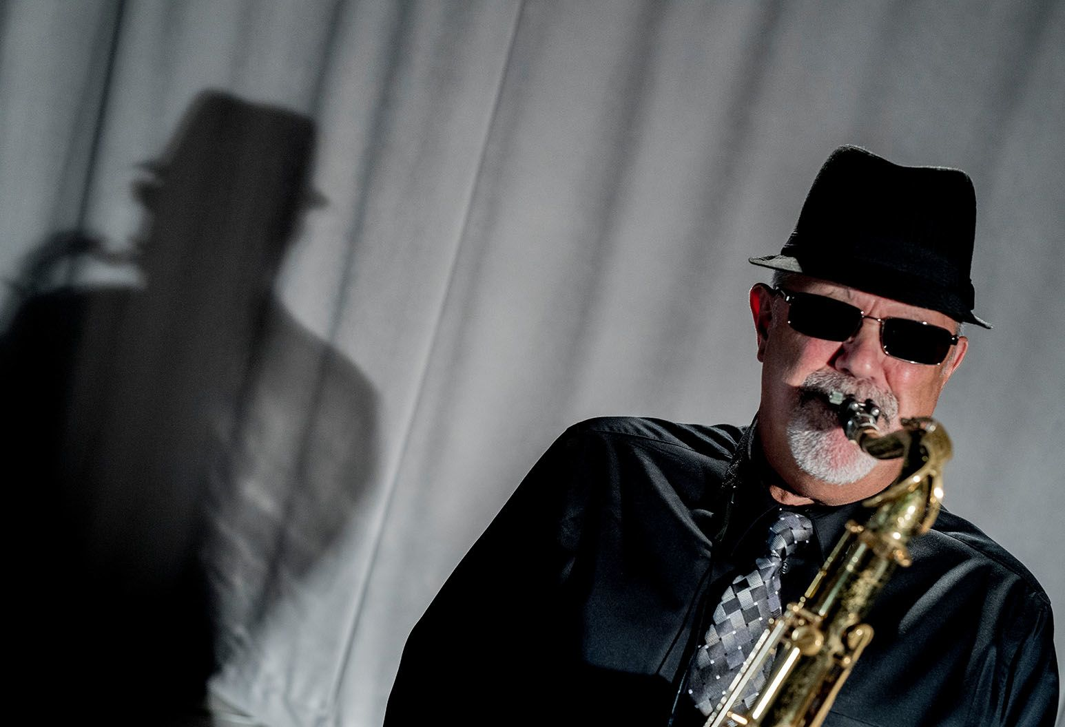 Man in sunglasses and fedora playing saxophone