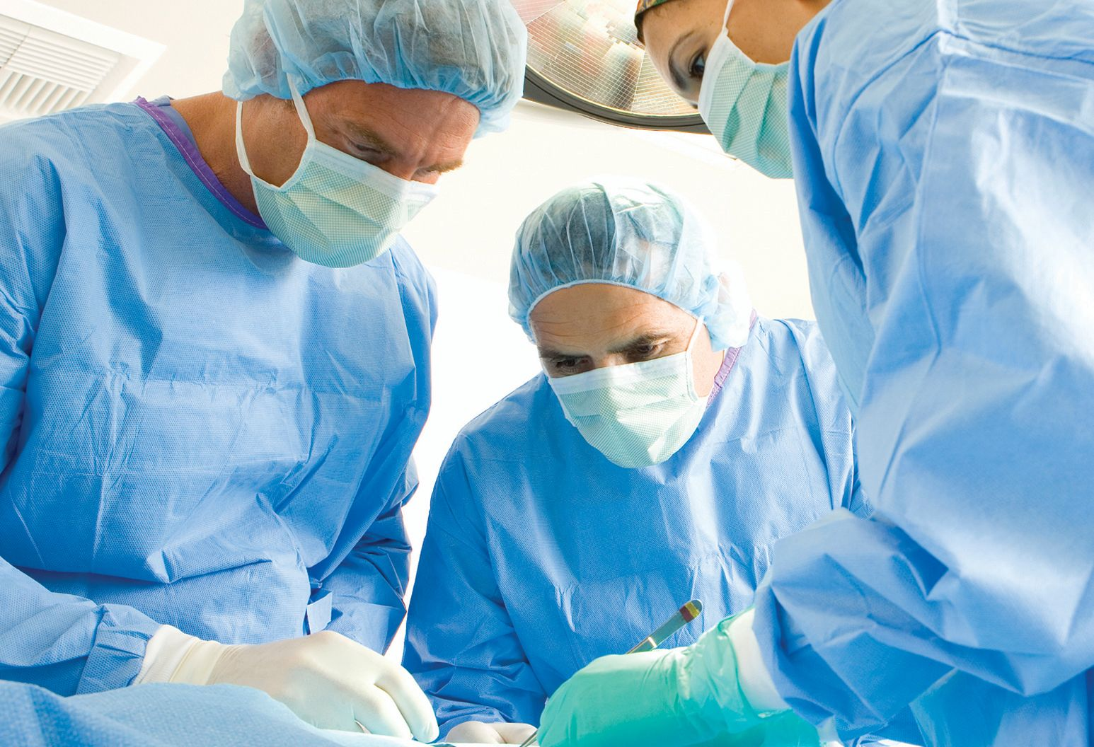 Two male and one female medical professionals in blue sterile gowns and masks stand over patient on operating table who is unseen.