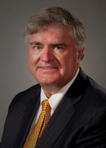 Laurence Kraemer wearing a gold tie and a striped suit