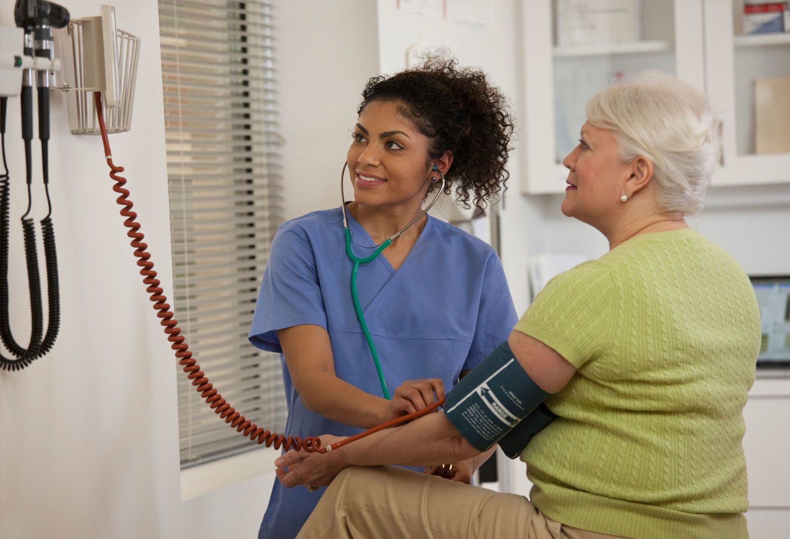 A young healthcare worker takes an elderly woman's blood pressure.