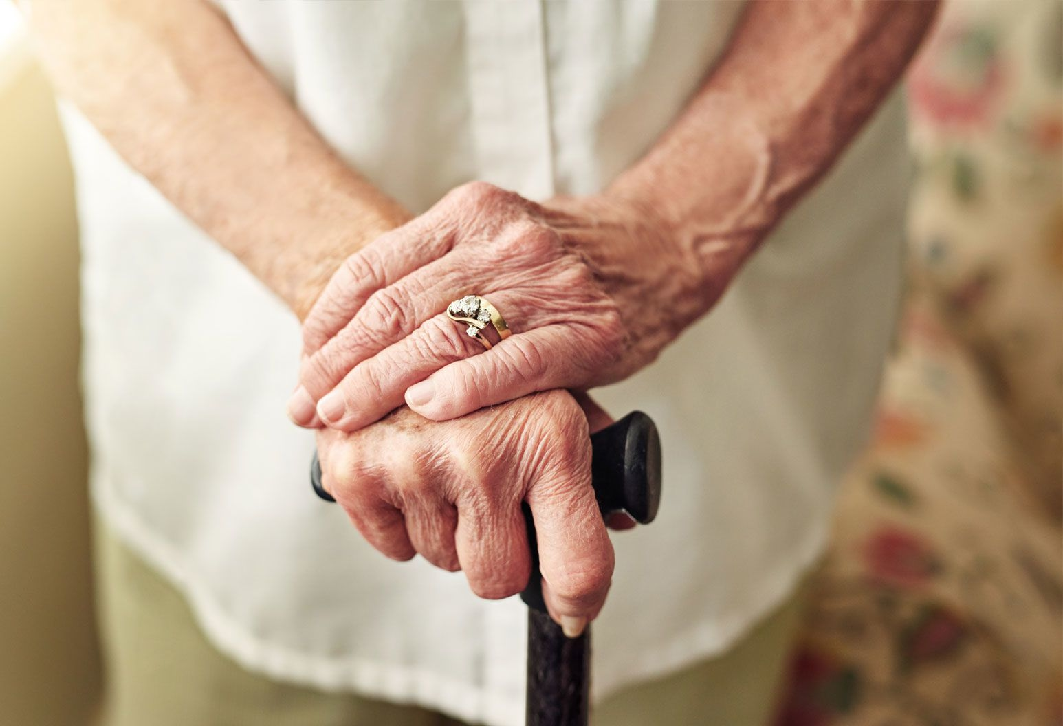 Close up of an elderly woman's hands holding a cane. She has a gold diamond ring on her finger. Her hands are in focus and the background is blurred. She's wearing a white button down shirt and tan pants.