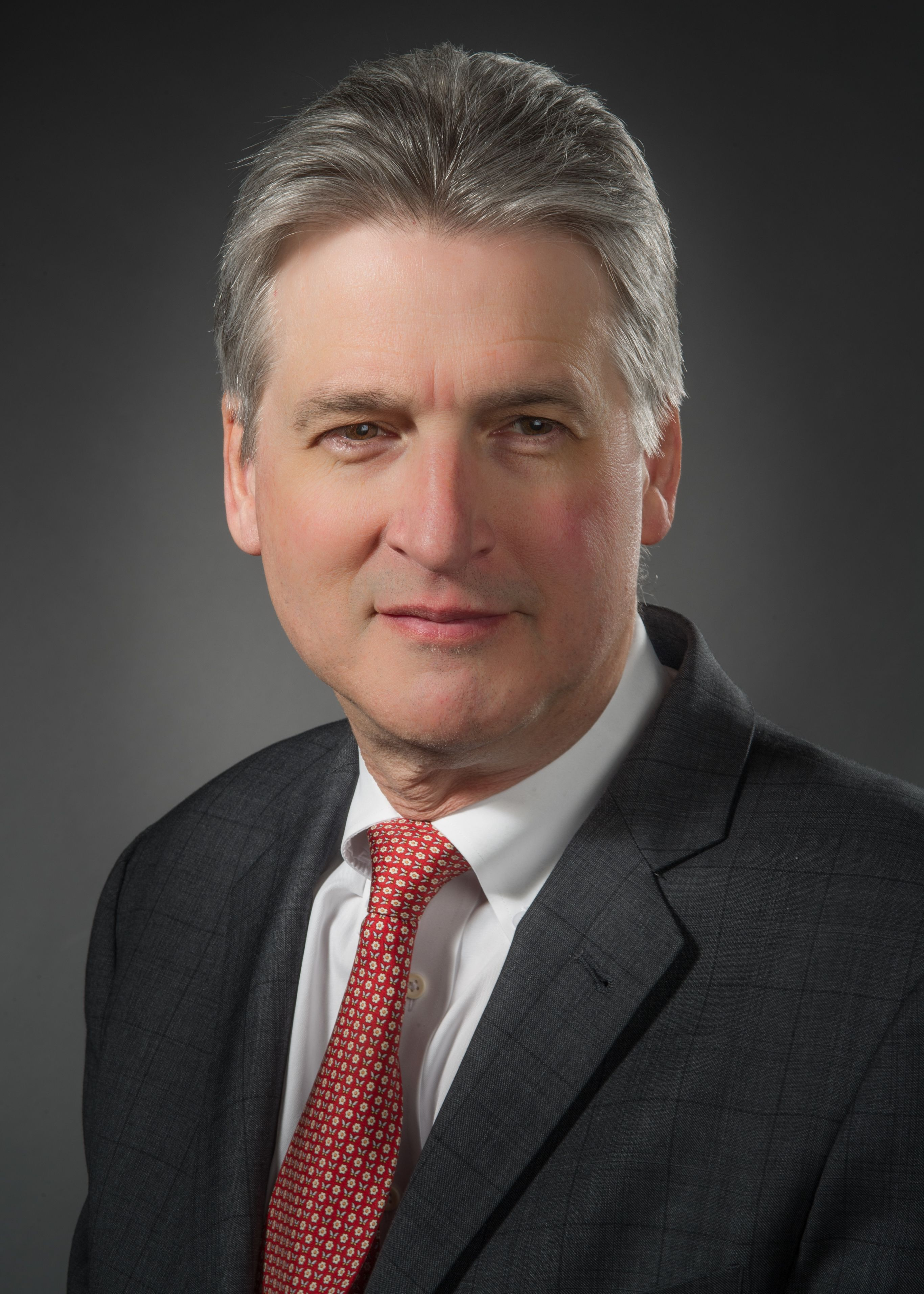 Martin Doerfler, MD, wearing a suit and a red tie