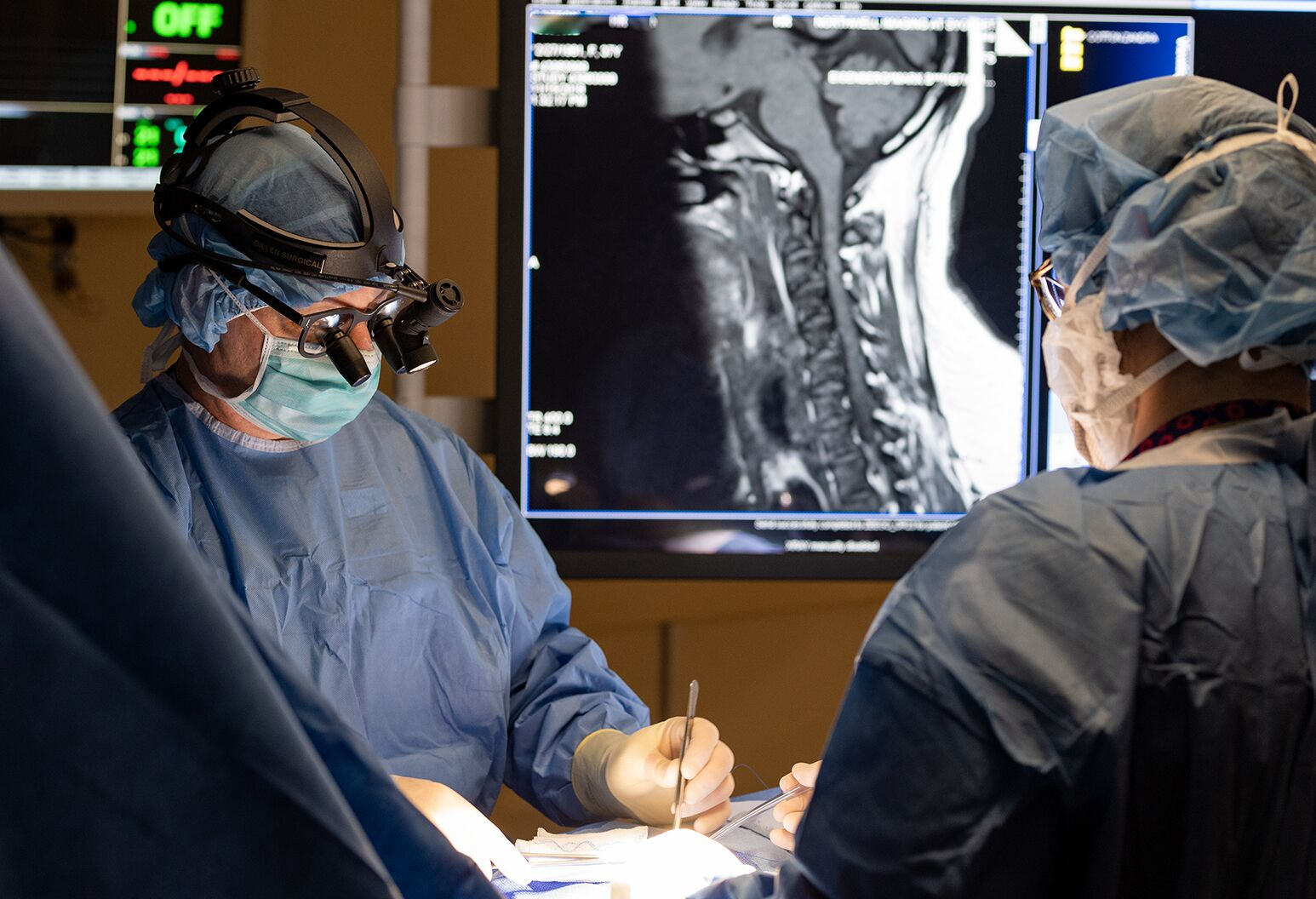 Two doctors performing spine surgery on a patient.