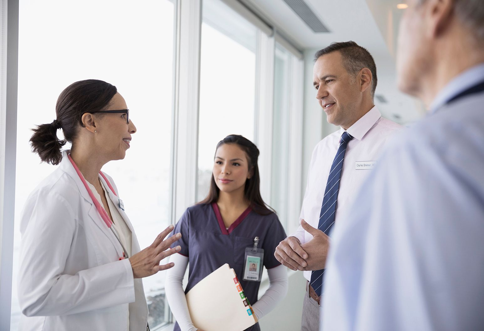 Two doctors conversing as a nurse joins in to hand one of the doctors a patients file