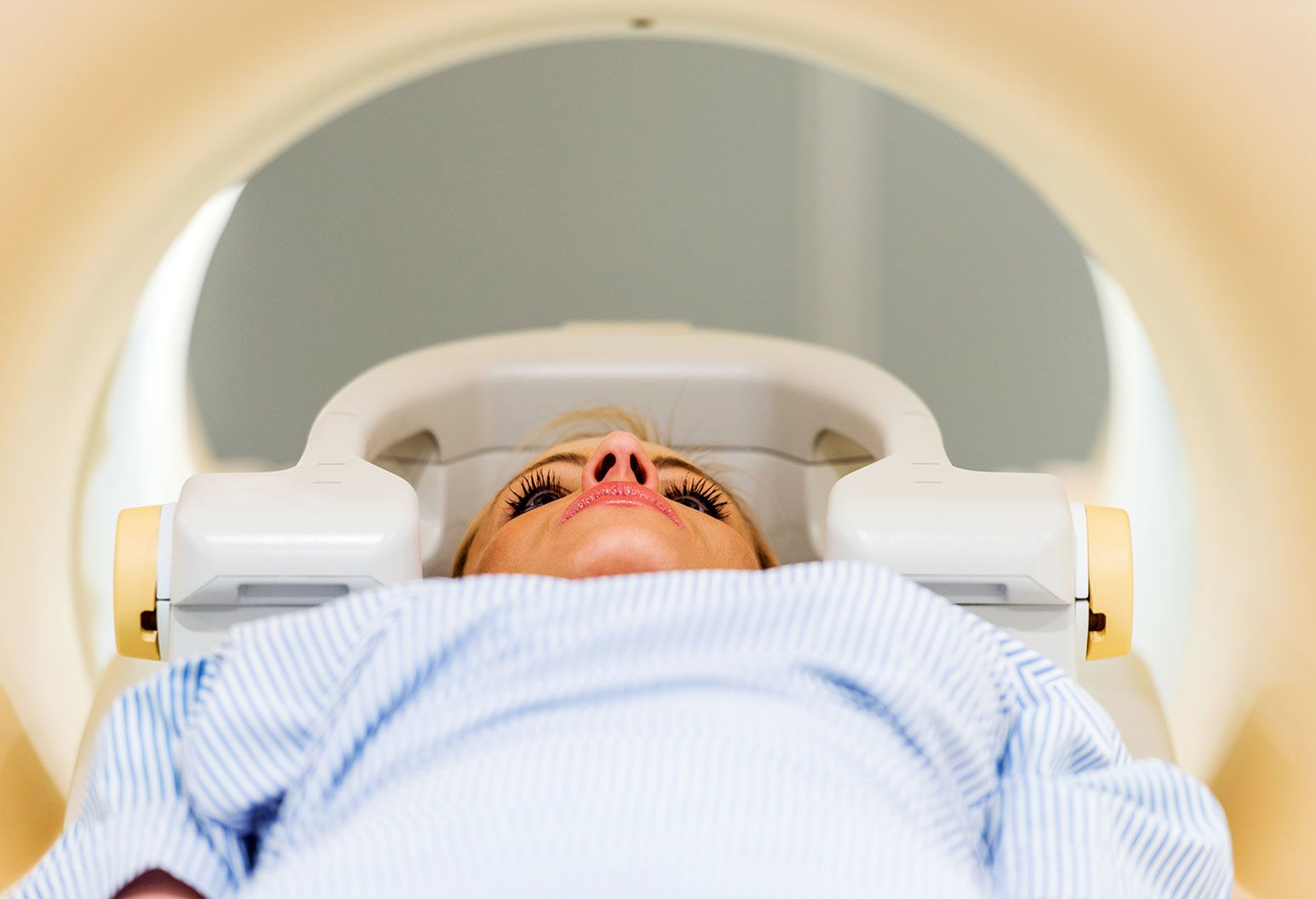 A woman in blue and white patient scrubs lies down on a platform inside a cylindrical white machine.