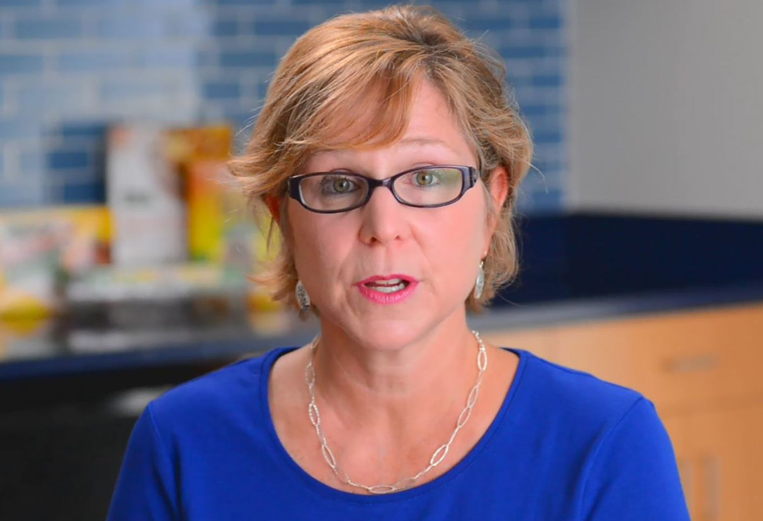 A middle-aged woman with short blonde hair is speaking. She's wearing a blue shirt and glasses.