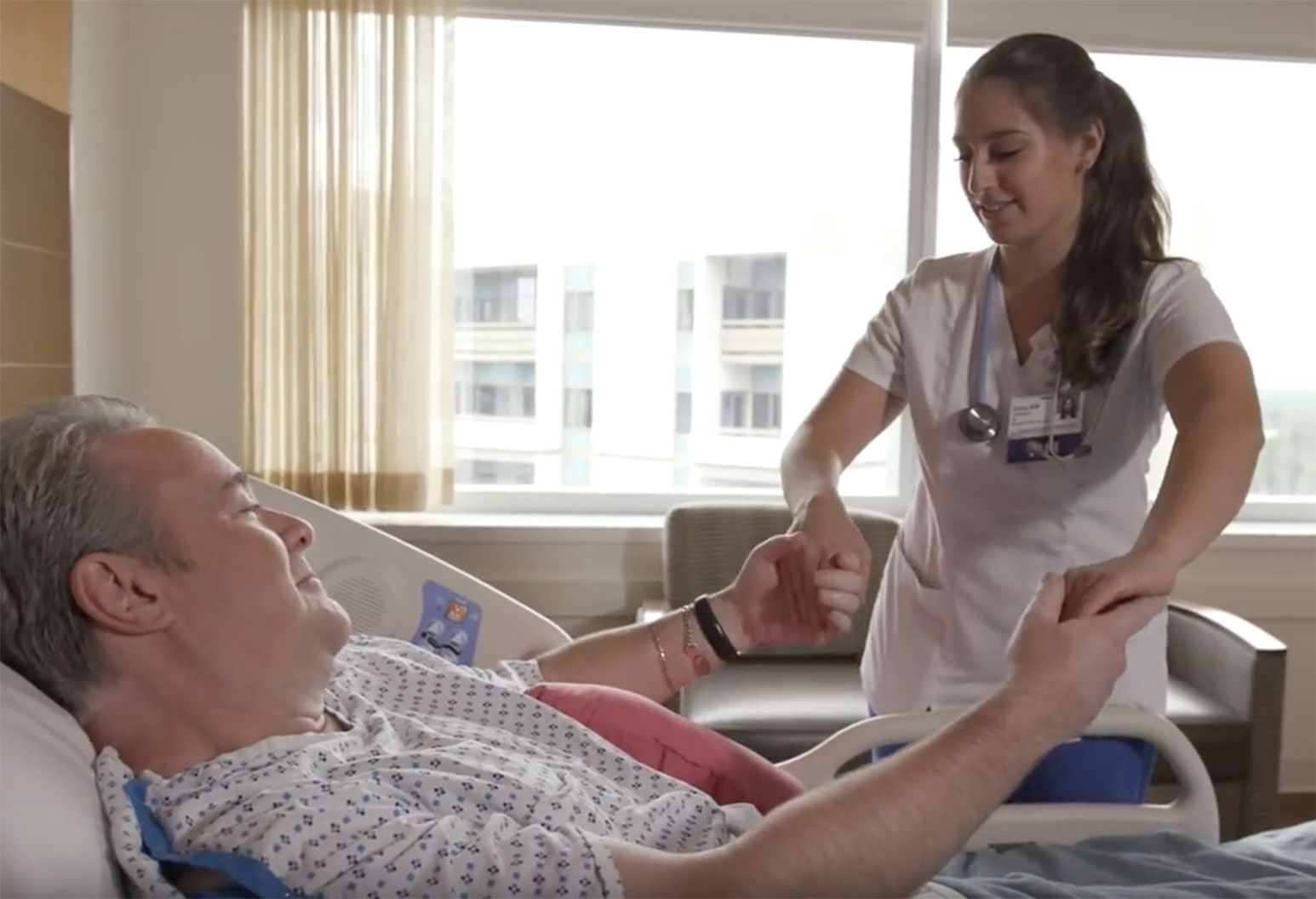 A smiling female nurse holds a male patient's hands as he reclines in a well-lit hospital room.