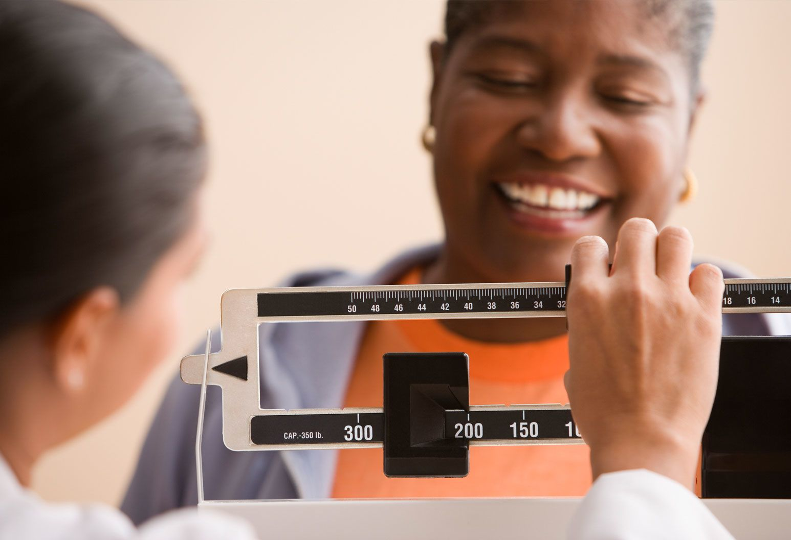 Female patient is smiling as she stands on a scale and her weight is measured