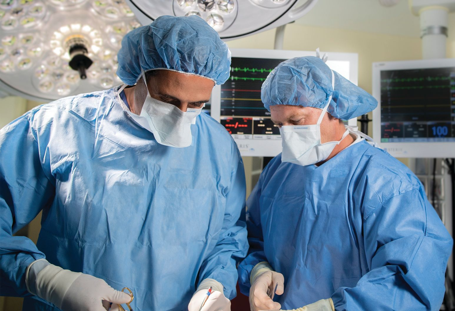 Two surgeons stand in operating room with masks over their mouths and equipment in background.