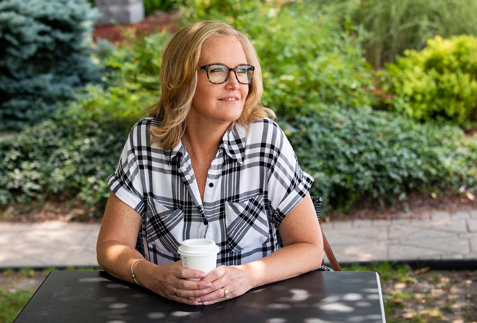 Blonde haired woman who had facial plastic surgery in plaid top and glasses, sitting with takeout coffee.