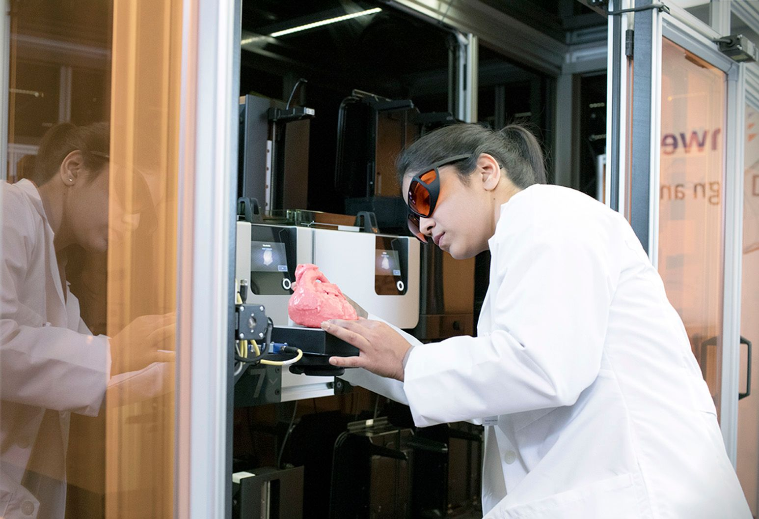 A female clinician in a white lab coat is in a lab standing in front of a 3D printing machine. She is holding a 3D printed model of a heart.