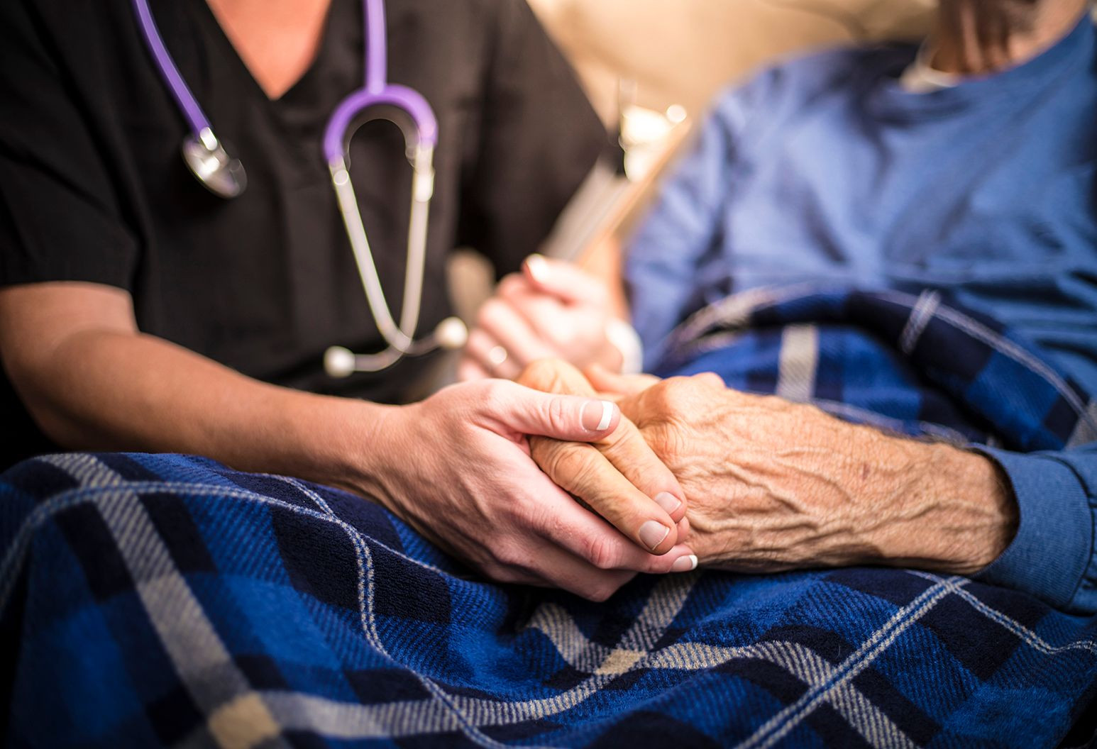 Hospice nurse is holding hand of an elderly male patient