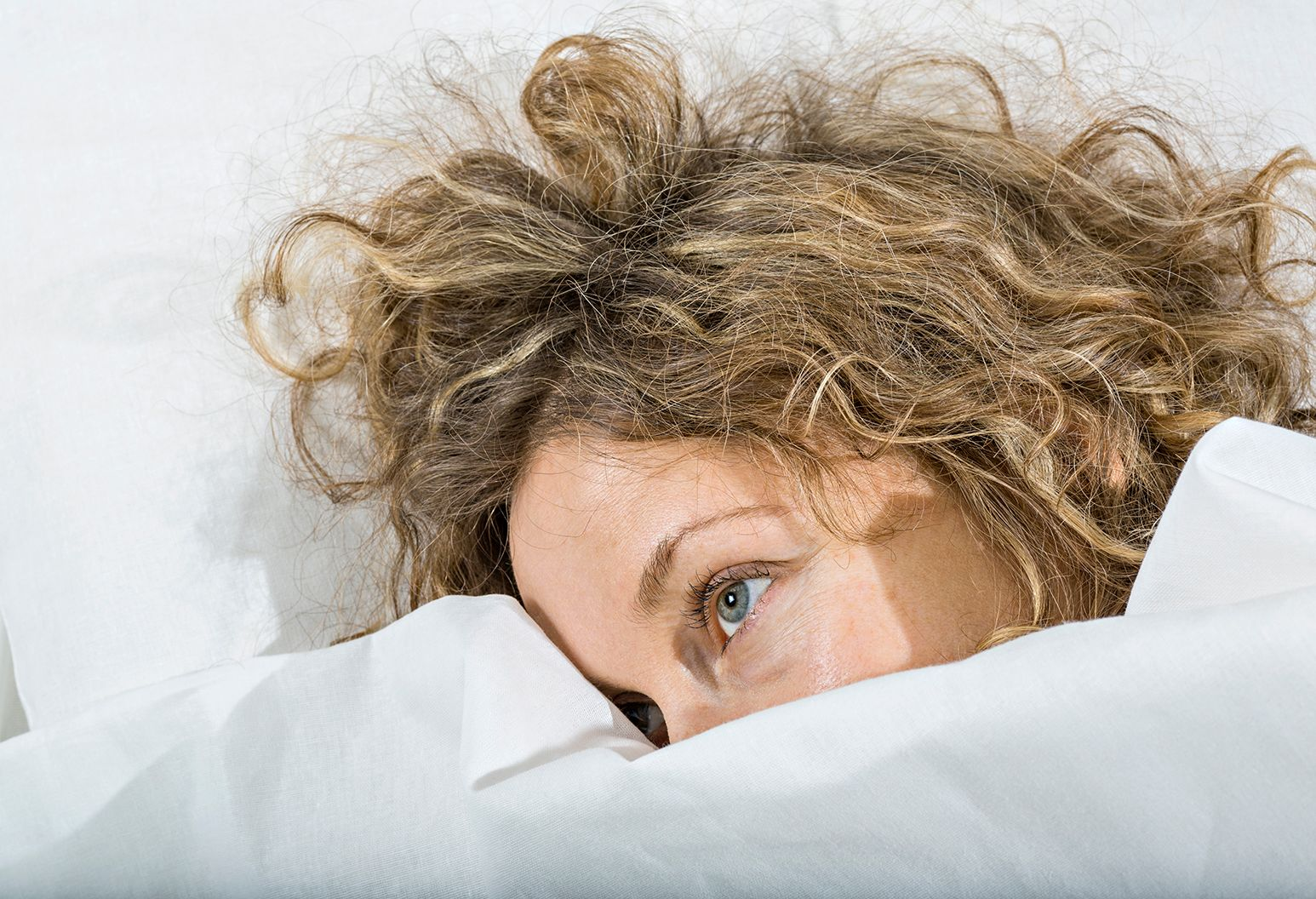 A woman lays in bed, mostly covered by her white bed sheets. Her hair is a mess and her blue eyes look tired and frustrated.