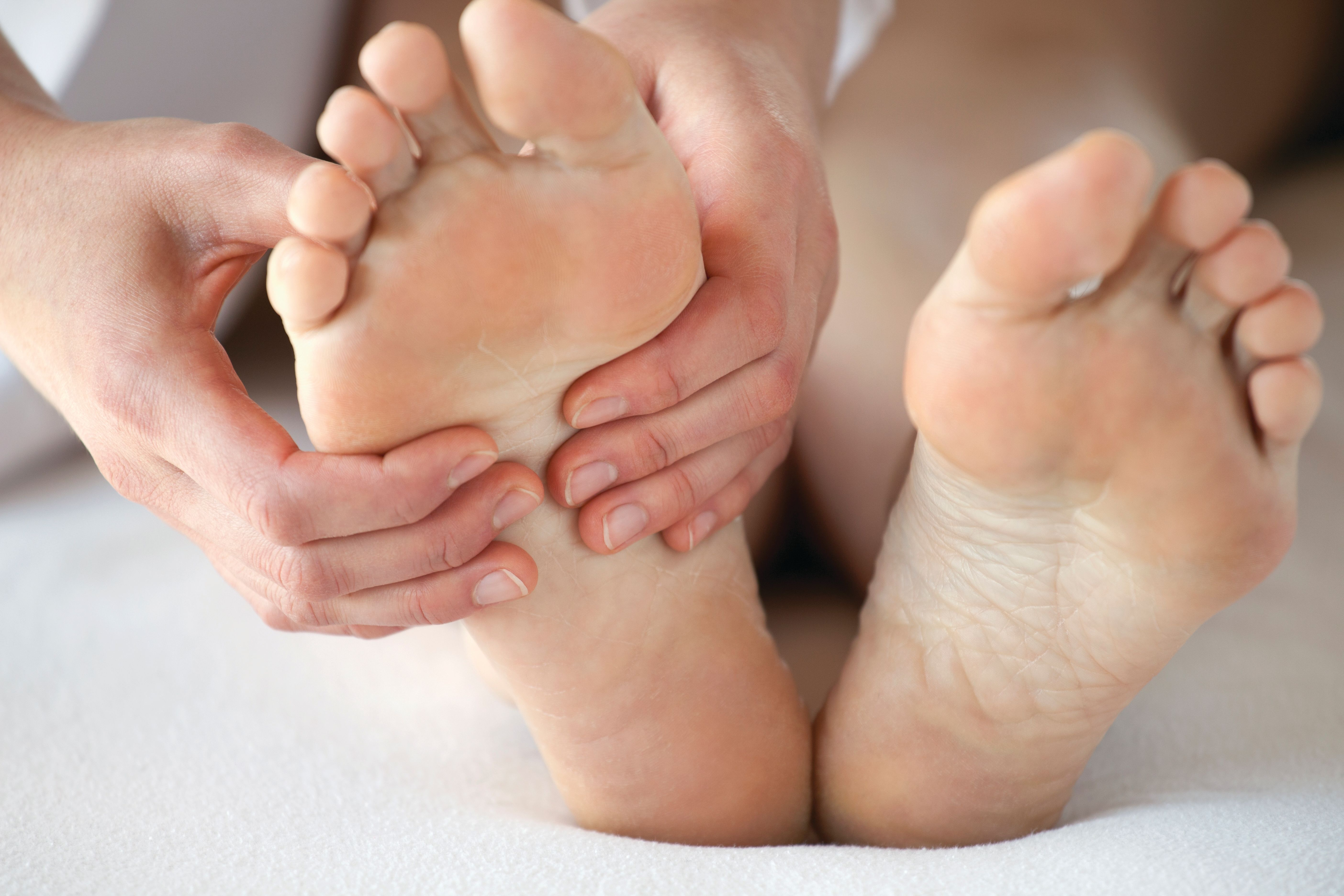 Close up of someone rubbing their bare feet