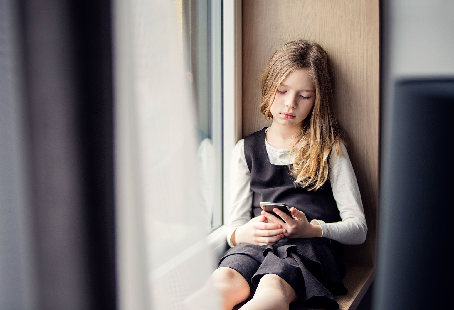 A girl in a grey shirt and black dress sits by the windowsill looking staring sadly into her phone.