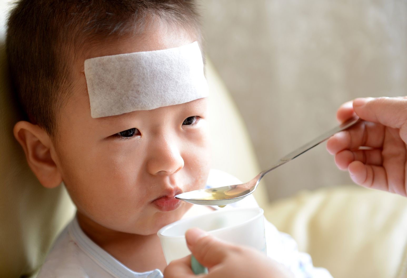 A 4 year old boy sits in bed with a cold compress on his forehead and as a teaspoon of tea is spooned into his mouth.