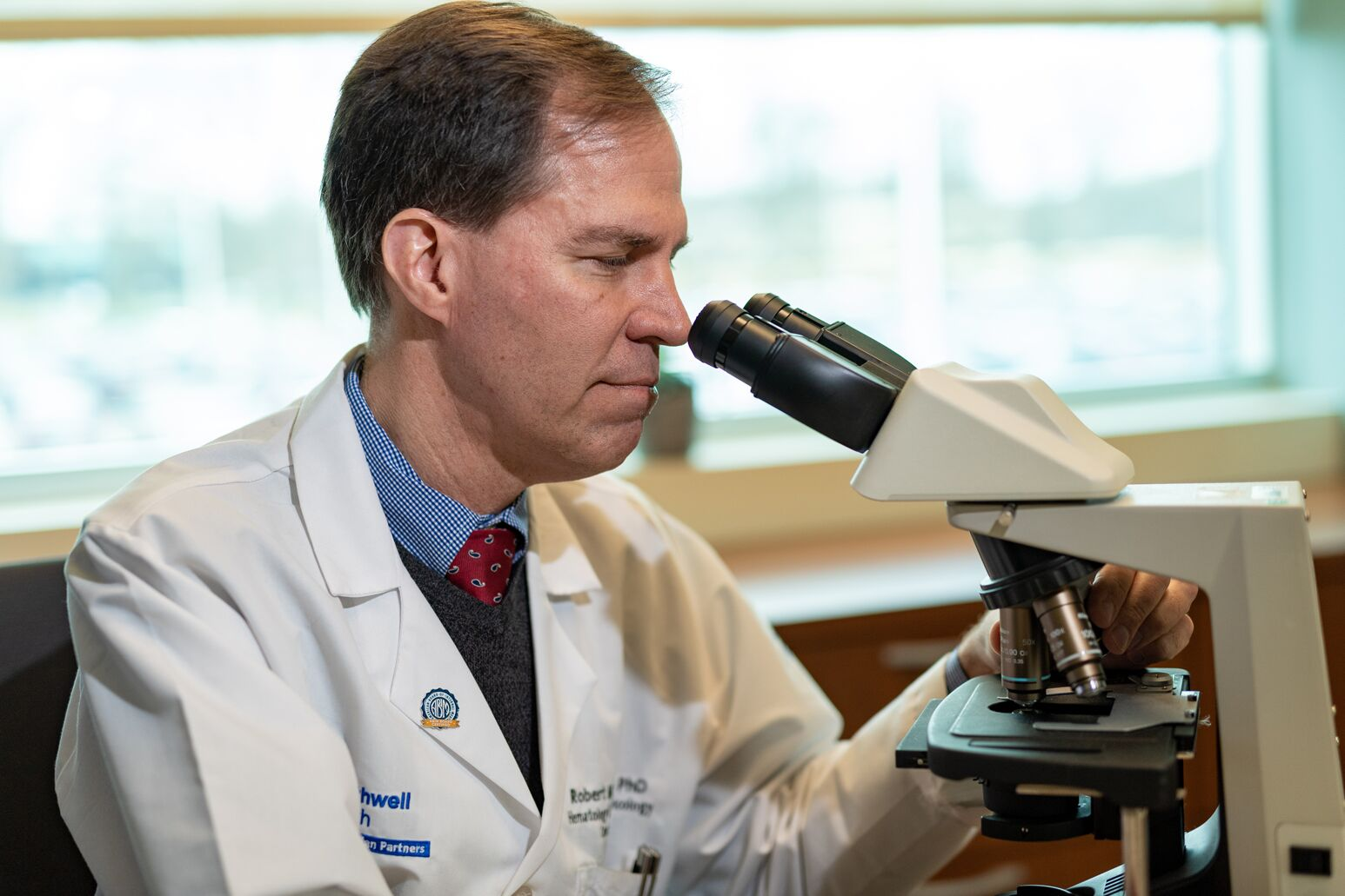 Robert Maki looks into a microscope. In this Q-and-A he discusses, clinical trials, Northwell's relationship with Cold Spring Harbor Laboratory and the war on cancer.