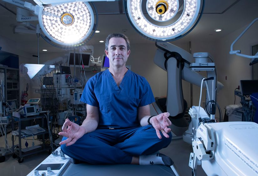 "John Boockvar, MD, wearing surgical scrubs, sits with his legs crossed in a meditative position on a surgical table surrounded by surgical equipment. Dr. Boockvar, MD, practices a type of mindfulness he classifies as ""gritflowness"" to manage the stresses of neurosurgery."