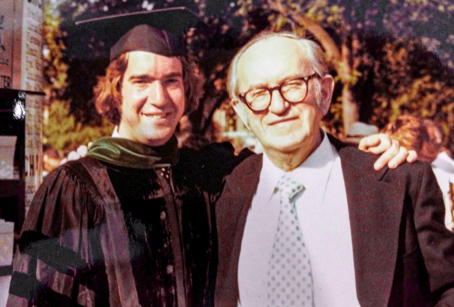 A young Dr. Rochelson, wearing graduation regalia, poses with his father.