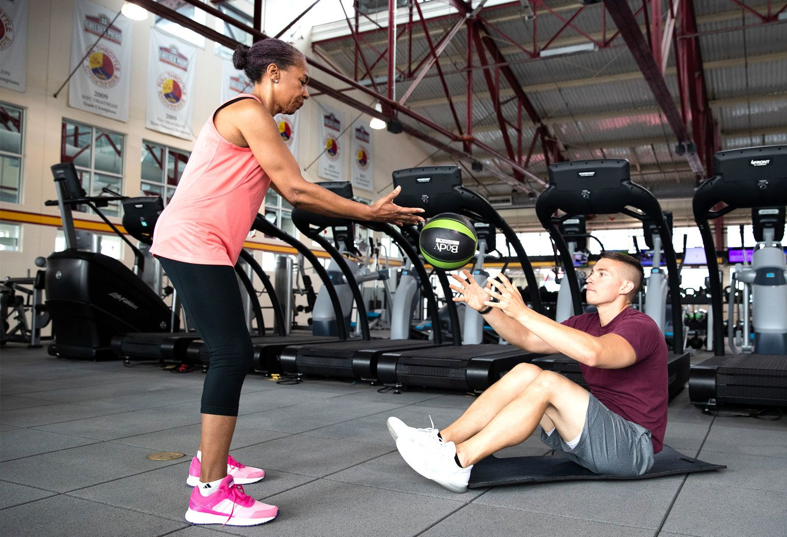 A young male and middle-aged female are working out together in a gym. The woman throws a work-out ball to the man.