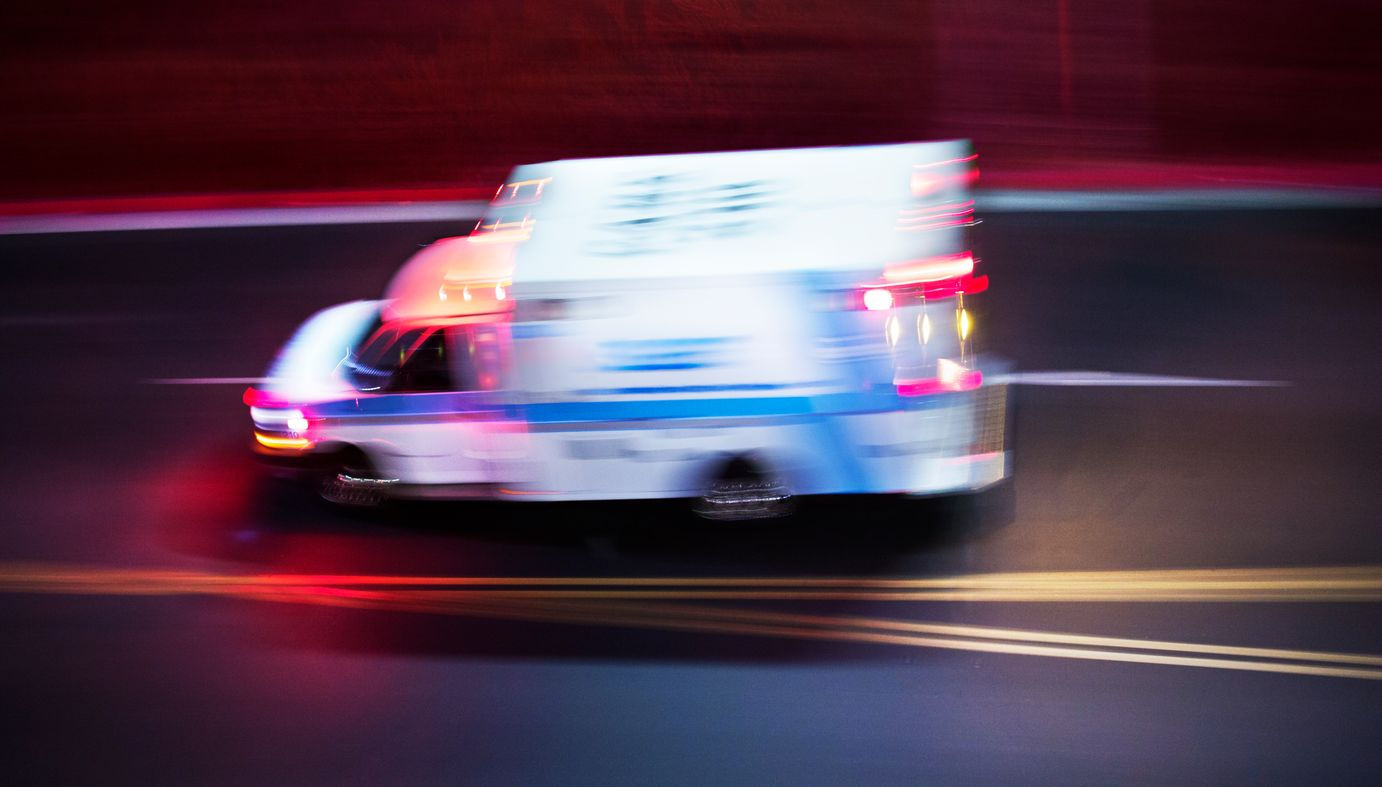 An ambulance rushes by in a blur of red, blue and yellow lights.
