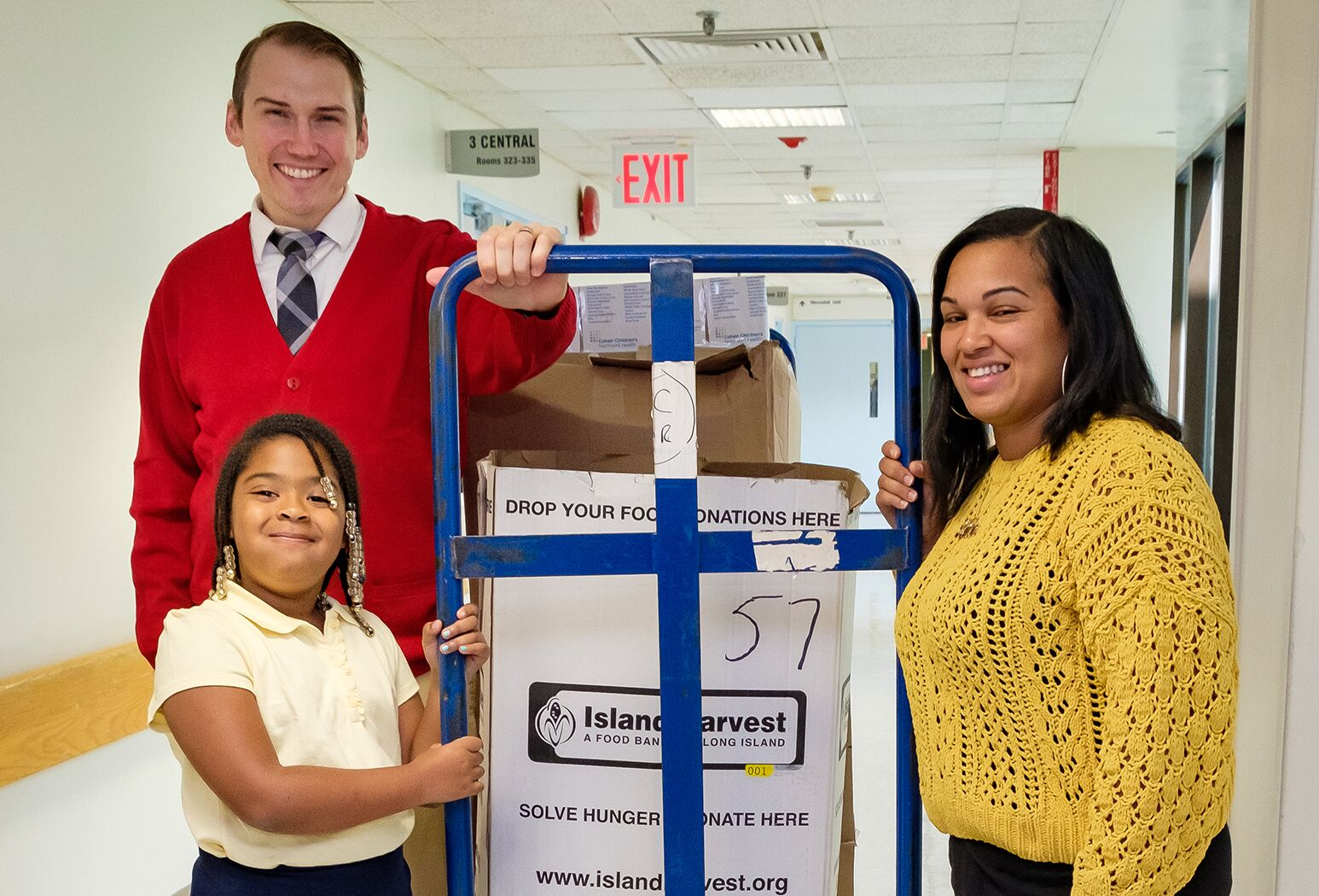From left: Mr. Rogers look alike Chris Kind helps 2nd grade student Tianna Huggins and her mother Nistachia Belle, of Roosevelt, LI, load some of the food collected for Island Harvest into a waiting truck.