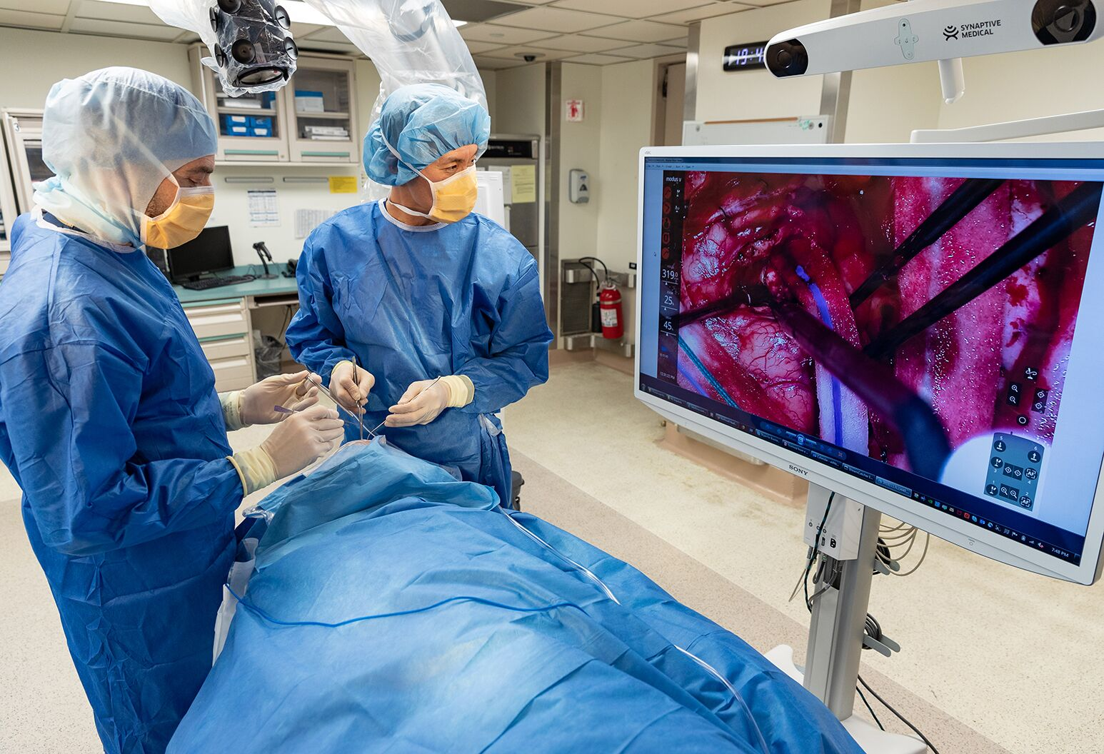 Two surgeons in an operating theatre look at a screen displaying a live feed of the brain surgery they are performing.