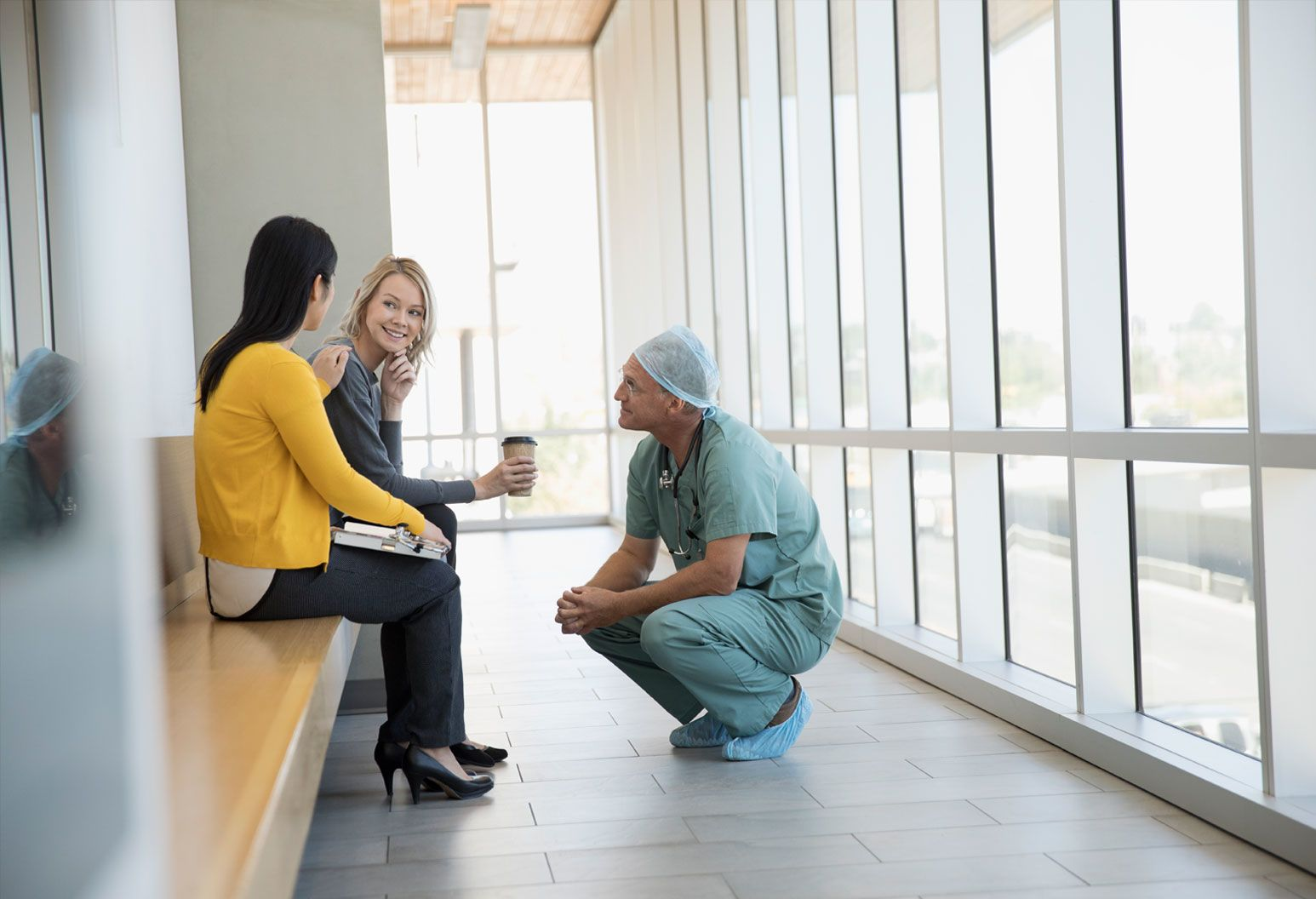 Surgeon talks to two women in waiting area of hospital.