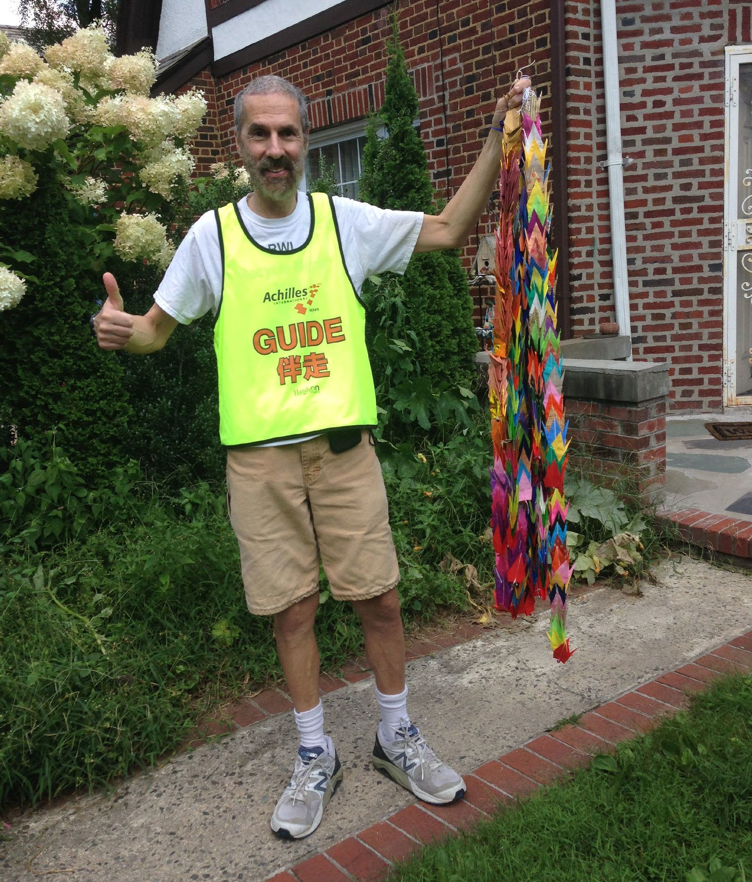 A tall skinny man wearing beige pants, a green vest, with a scraggly gray beard and shaved head gives a numbs up at the camera with one hand while holding a ribbon of paper cranes on the other.