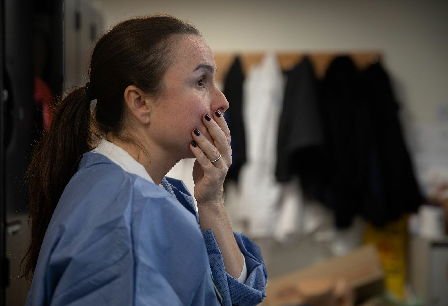 A woman with long tied up hair, stands against a locker wearing blue scrubs with her hand covering her mouth.