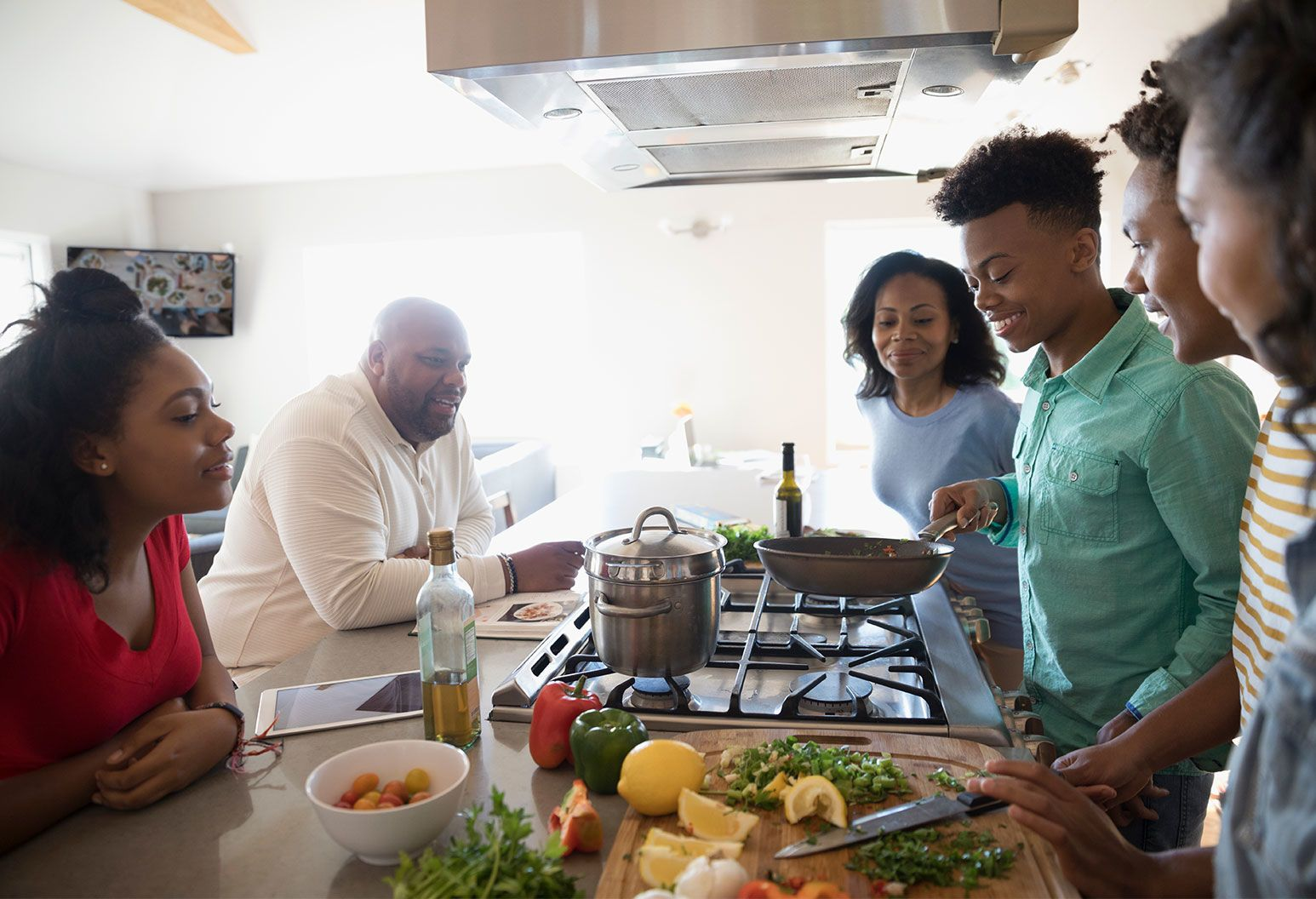 A family gathers around a cooking table. A teenage boy holds a frying pan above the stove as his family watches on and smiles.