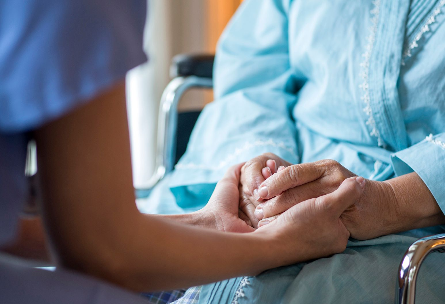 A medical professional's hands are seen up close, as they cradle the hands of an older patient.