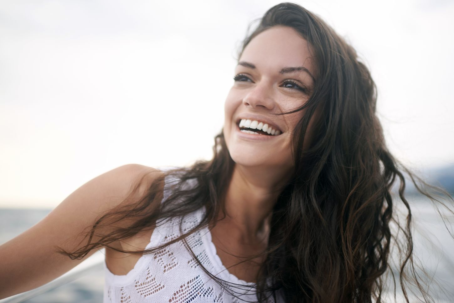 A woman looks off into the distance with a big smile on her face. Her long brown hair flows around her, and she wears a white tank top with thick straps. Only her shoulders and face are visible.
