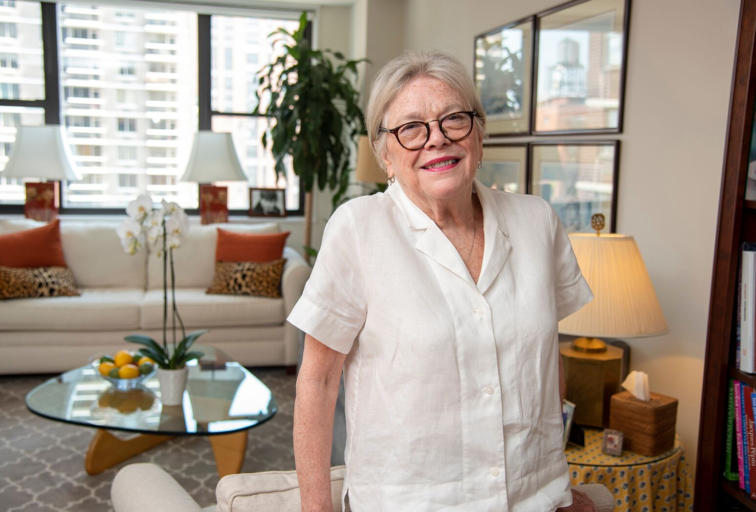 Woman with gray hair and black glasses in white blouse in front of a coffee table and couch.