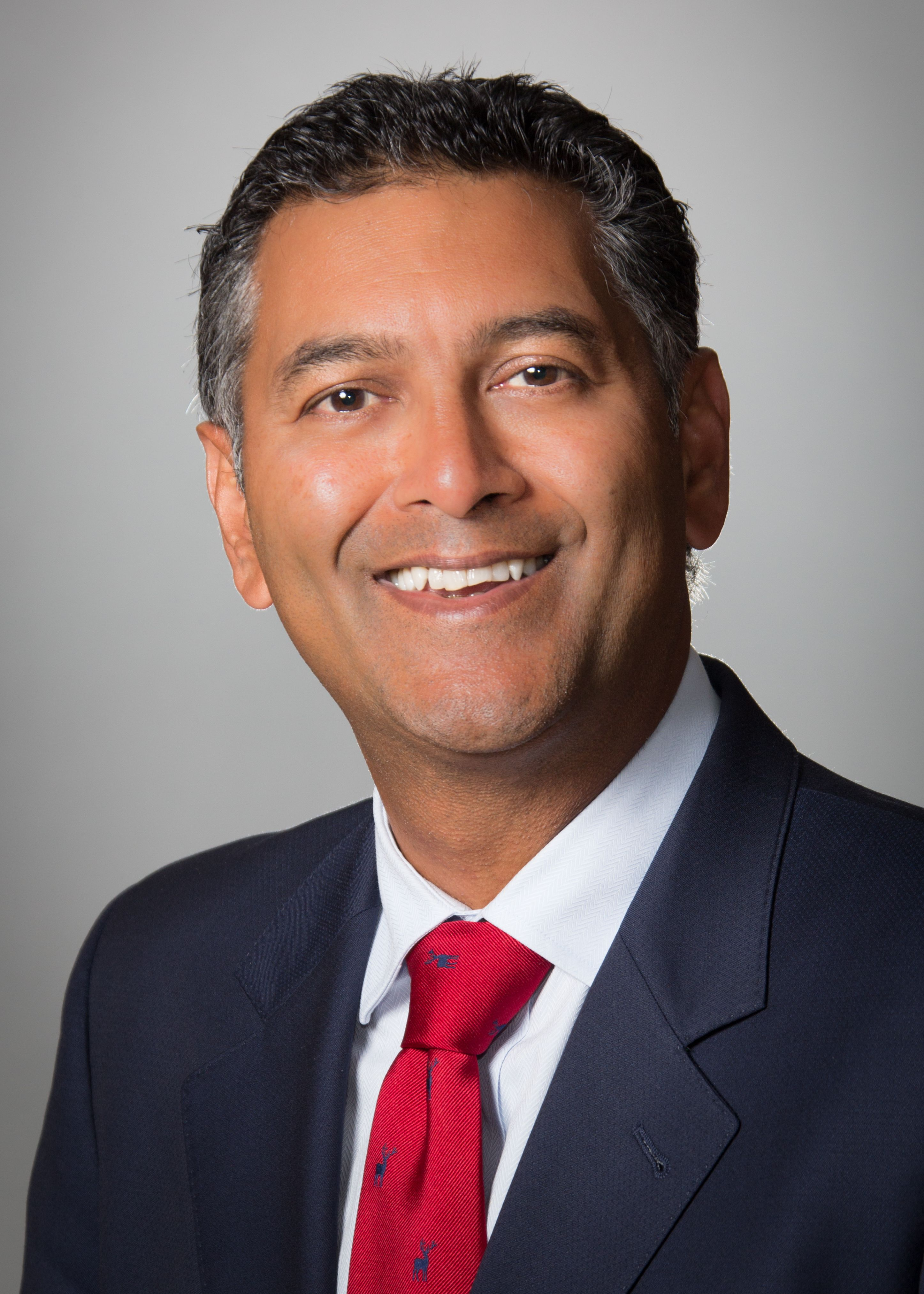 Varinder Singh, MD, wearing a suit and red tie