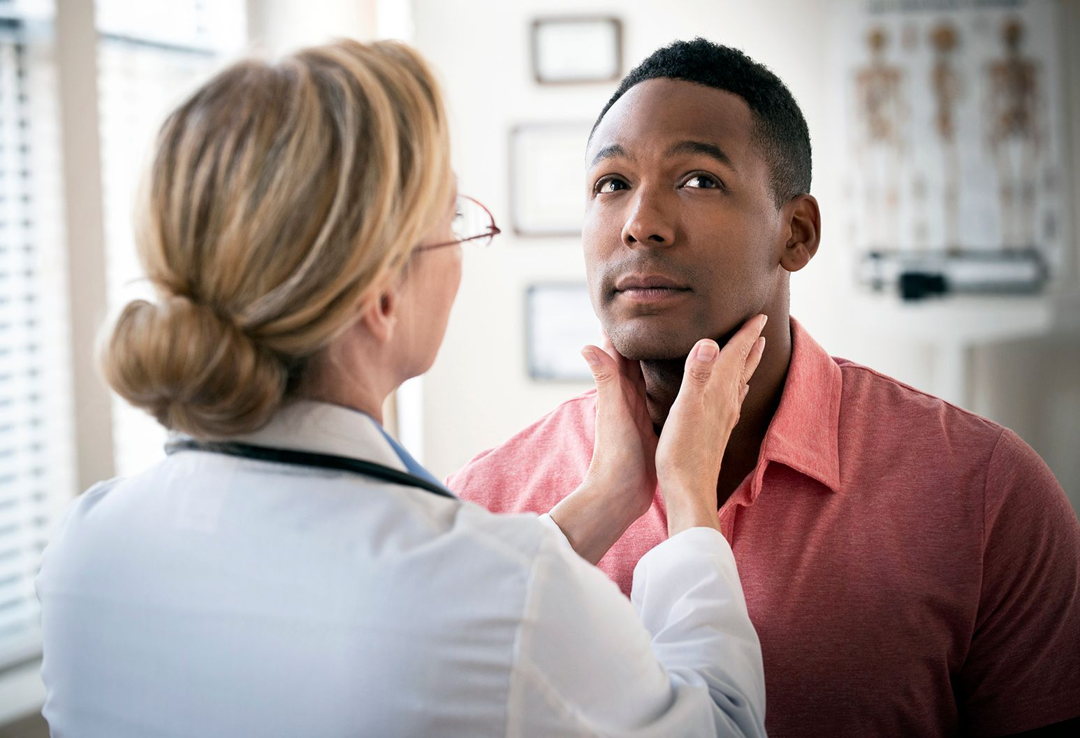 A man in a pink collared shirt looks up as a female doctor feels the area under his jaw.