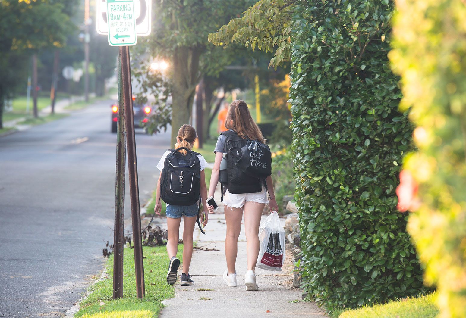 Kids walking to school - Two girls are walking on a sidewalk carrying black schoolbags on their back.