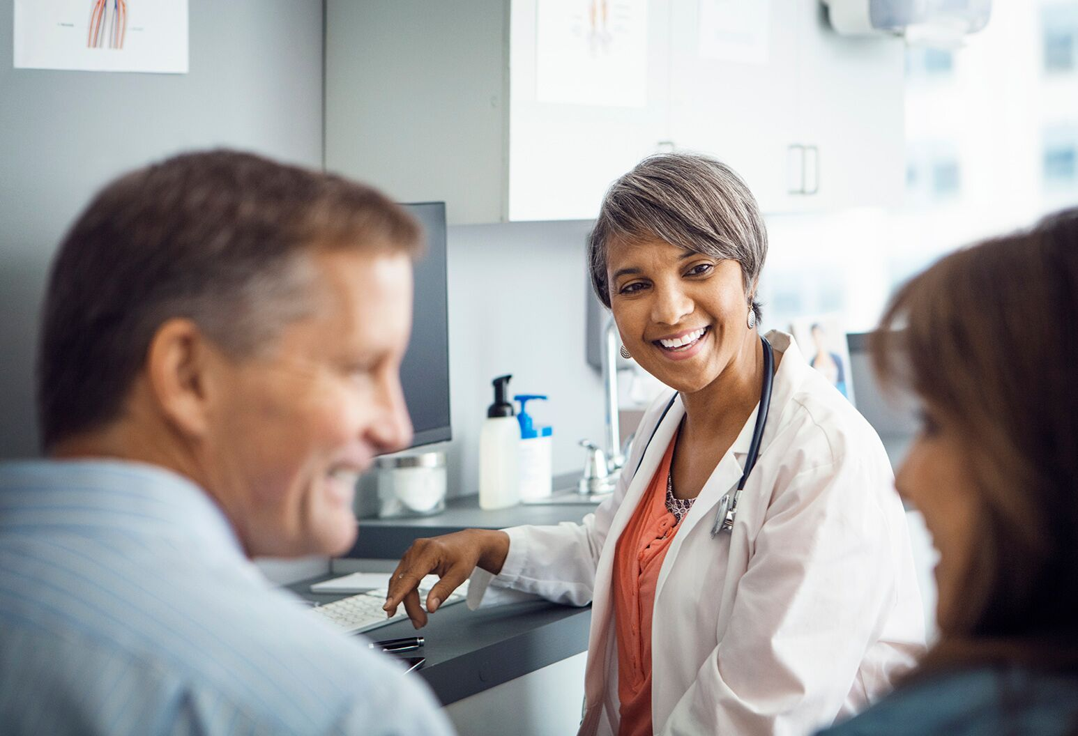 Female doctor smiling while seeing patients in the exam room.
