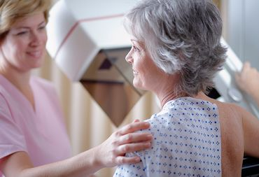 A nurse in pink scrubs prepares her patient for the breast MRI test she is about to recieve