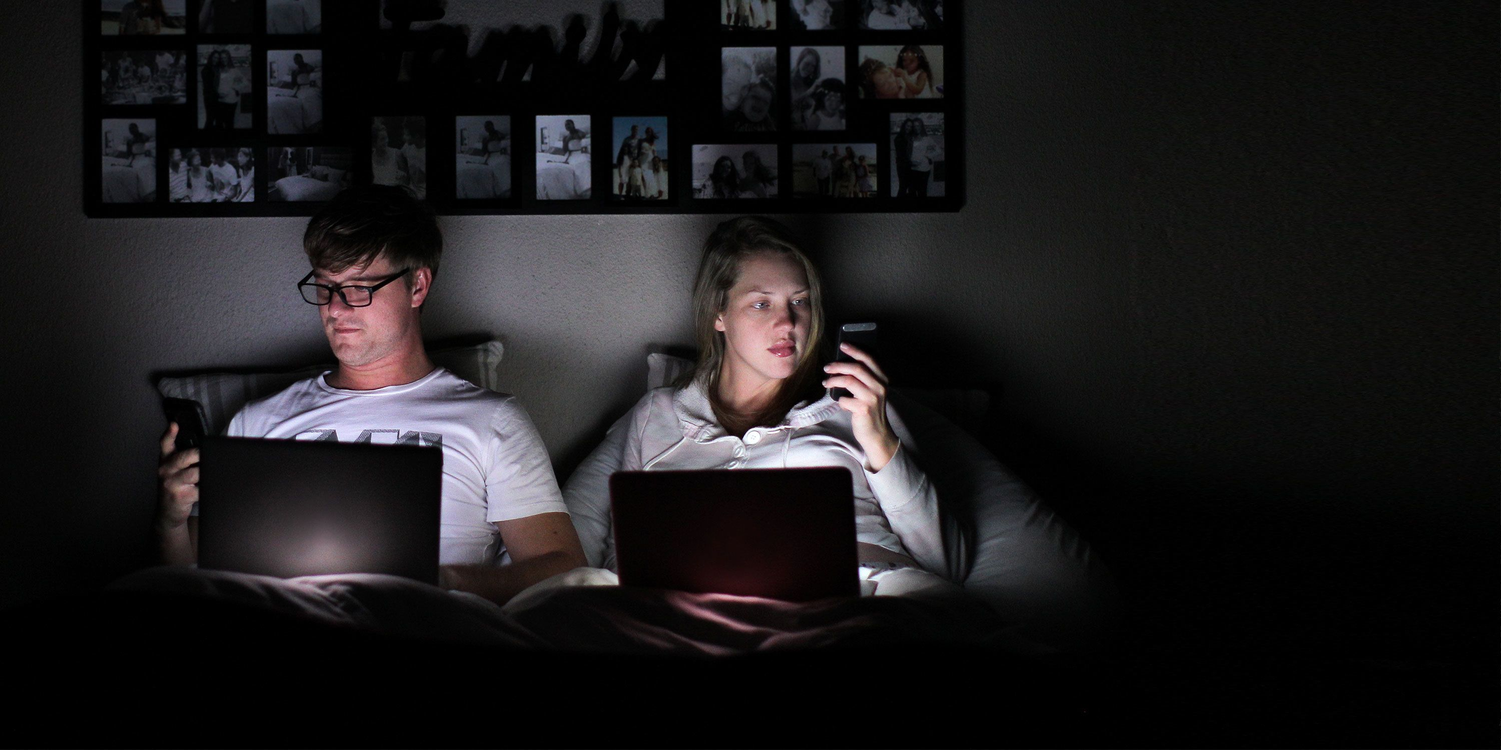 A man and woman sit together in the dark on their bed against a wall. They both have laptops open on their lap and are looking at their cellphones not interacting with each other.