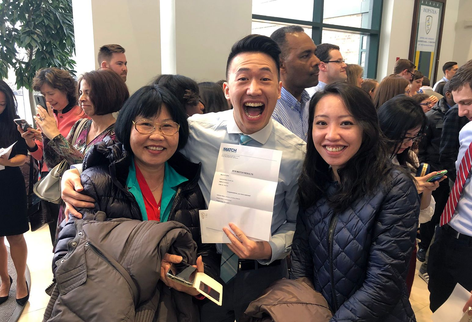 A student, with his family, holding a letter ecstatic about being matched for his residency.