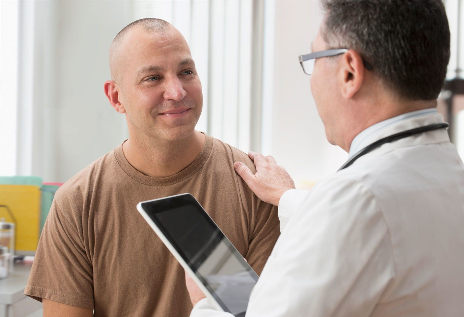 A male doctor rests his hand on a male patient's shoulder