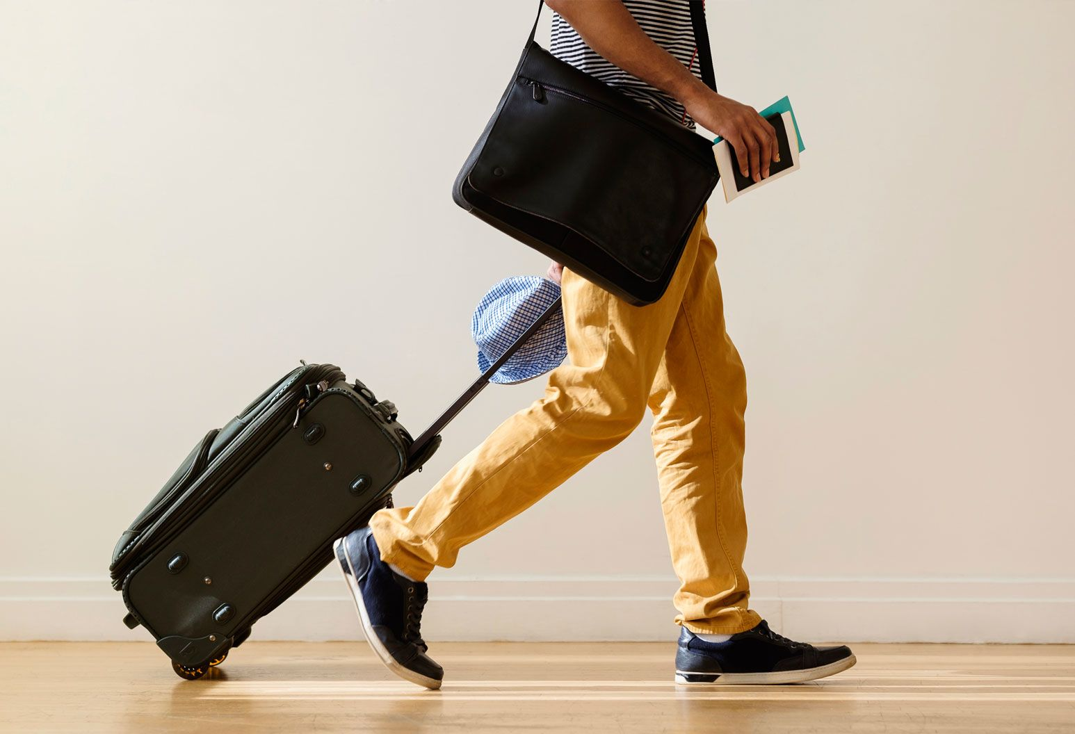 A man rolling a suitcase and holding a passport is walking. He wears a striped t-shirt, tan pants and black sneakers. He has a computer bag on his shoulder and looks like he's travelling.