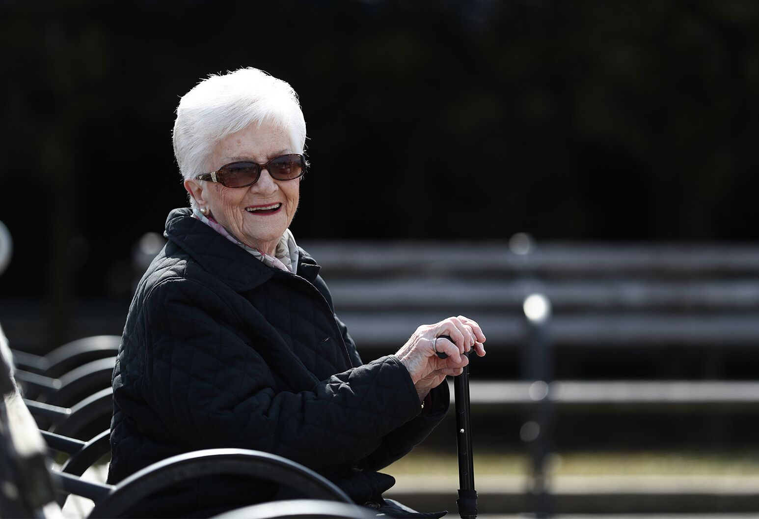 90-year-old woman wearing sunglasses sits on a bench in a park.